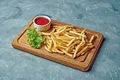 French fries on wood board on gray background
