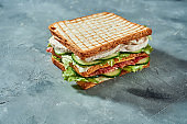 Double toast with chicken, cucumbers and salami on gray background. Selective focus on tasty sandwich