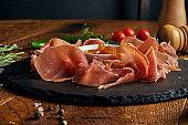 Classic antipasto - jamon crudo on a black slate tray on a wooden background