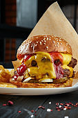 Appetizing and juicy burger with beef, melted cheddar cheese, ketchup, onions and pickled cucumbers on a white plate with french fries. Close up, vertical