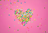 Heart shape made of colorful confetti. Pink backdrop with scattered paper circles. Beautiful decor for the party. Festive backgrond for love story. Valentine's day symbol. View from above. Flat lay.