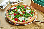 Appetizing baked pizza with salmon, cherry tomatoes, parmesan and arugula with crispy crust on a wooden background. Restaurant table setting. CLose up