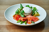 Tasty and healthy continental breakfast - quinoa with benedict eggs, spinach, avocado, salted salmon and asparagus in white bowl. Wooden background