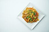Tasty udon noodles in sweet and sour sauce with vegetables and chicken meat plate on a gray background. Top view with copy space
