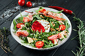 Delicious salad with grilled camembert, arugula, spinach, jamon, cherry tomatoes in white on a black background. Close up