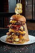 Huge burger tower with 5 beef cutlets, melted cheese, onions, potatoes, cucumbers, sauce. Close up, vertical