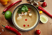 Top view tom yam with seafood in composition with ingridients. Popular hot and sour Thai soup. Copy space. Flat lay with spicy and tasty food. Banner or menu photo. Tom yum