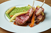 Rack of medium rare lamb with a side dish of green puree and baby corn and carrots on a white plate on a wooden background. Close up