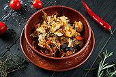 Rice wok noodles with seafood (squid chips, shrimps) soy sauce and vegetables in a ceramic bowl on a black background. Close up