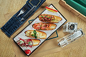 Assorted varied bruschetta on a white plate. White baguette with jamon, toast with tomato salsa, bruschetta with salmon and blue cheese. Restaurant table setting. Top view