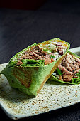 Close up view on burrito with beef, rice, tomatoes, corn and bell pepper in green pita on a brown plate with tomato salsa and guacamole. Vegetarian Shawarma Roll