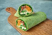 Vegetarian shawarma. Roll in green pita with quinoa, sweet potato, lettuce and tofu on a board