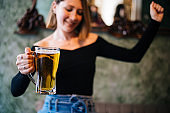 Beautiful woman drinking beer and dancing