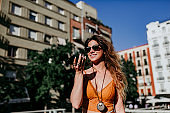 Beautiful young caucasian woman walking at the city street on a sunny day. Sending an audio with mobile phone. Happy face smiling. Urban lifestyle