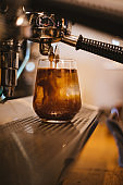 Espresso pouring into glass filled by ice