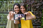 two beautiful women outdoors taking a selfie with mobile phone. They are laughing. lifestyle and friendship concept