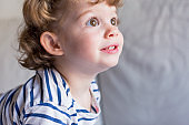beautiful little girl standing on bed and smiling. Fun, home, indoors. Lifestyle