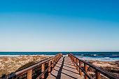 beautiful beach landscape at sunset. wooden bridge path. blue sky