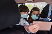Girl wearing masks in a car and taking selfie