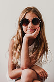 Portrait of beautiful teenager girl at home. Sitting and wearing modern sunglasses. white background. Happiness and lifestyle concept
