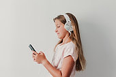 Portrait of a cheerful cute teenager girl listening music in mobile phone and headphones. white background. Happiness, music and lifestyle concept