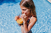 beautiful teenager girl at the pool drinking healthy orange juice and having fun outdoors. Summertime and lifestyle concept