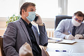 Serius man wearing protective mask and gloves concentrating on his phone conversation at office