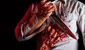 Murderer in bloody splattered white shirt holding kitchen knife.