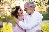 Beautiful senior couple in love outside in spring nature, hugging.