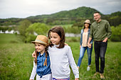Happy family with two small daughters walking outdoors in spring nature.