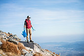Man hiker picking up litter in nature in mountains, plogging concept.