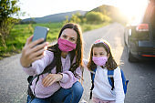 Mother with small daughter taking selfie on trip outdoors in nature, wearing face masks.