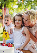 Small girl with cake celebrating birthday outdoors in garden in summer, party concept.