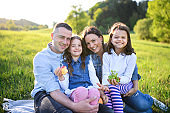 Happy family with two small daughters sitting outdoors in spring nature, having picnic.