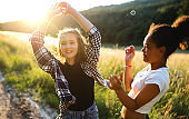 Young teenager girls friends outdoors in nature at sunset, blowing bubbles.