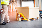 Worker unloading cargo pallet shipment goods, package box, his is using hand pallet jack load into a truck, Road freight transport, Warehouse industrial delivery shipment and logistics