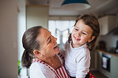 Small girl with senior grandmother in kitchen indoors at home.