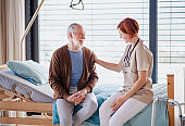 A female doctor talking to senior patient in bed in hospital.