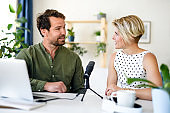 Happy couple with microphone having video call on laptop indoors at home.