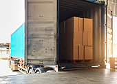 Warehouse delivery shipment on road by truck, stack package boxes on pallet load into a truck.