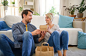Happy couple sitting on floor indoors at home, fast food delivery concept.