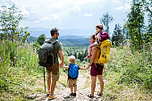 Rear view of family with small children hiking outdoors in summer nature, resting.