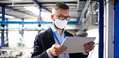 Technician or engineer with protective mask and tablet working in industrial factory.