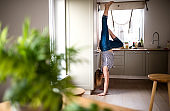 Young woman doing sport indoors at home, handstand.