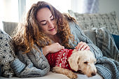 Young woman relaxing indoors on sofa at home with pet dog.