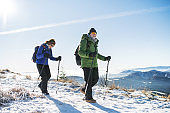 Senior couple with nordic walking poles hiking in snow-covered winter nature.