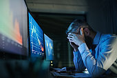 Frustrated businessman with computer sitting at desk, working late. Financial crisis concept.