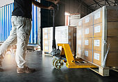 Shipment, Delivery, Cargo export Worker unloading heavy pallet goods, his using hand pallet jack loading into container truck. Road freight cargo transportation and Logistics.