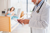 Unrecognizable doctor standing in hospital room, using tablet.