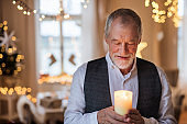 Front view of happy senior man indoors holding candle at Christmas.